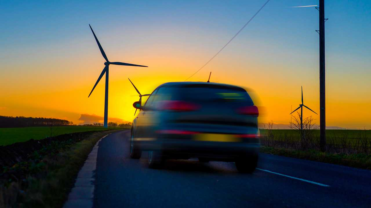 Car driving towards wind turbines at sunset