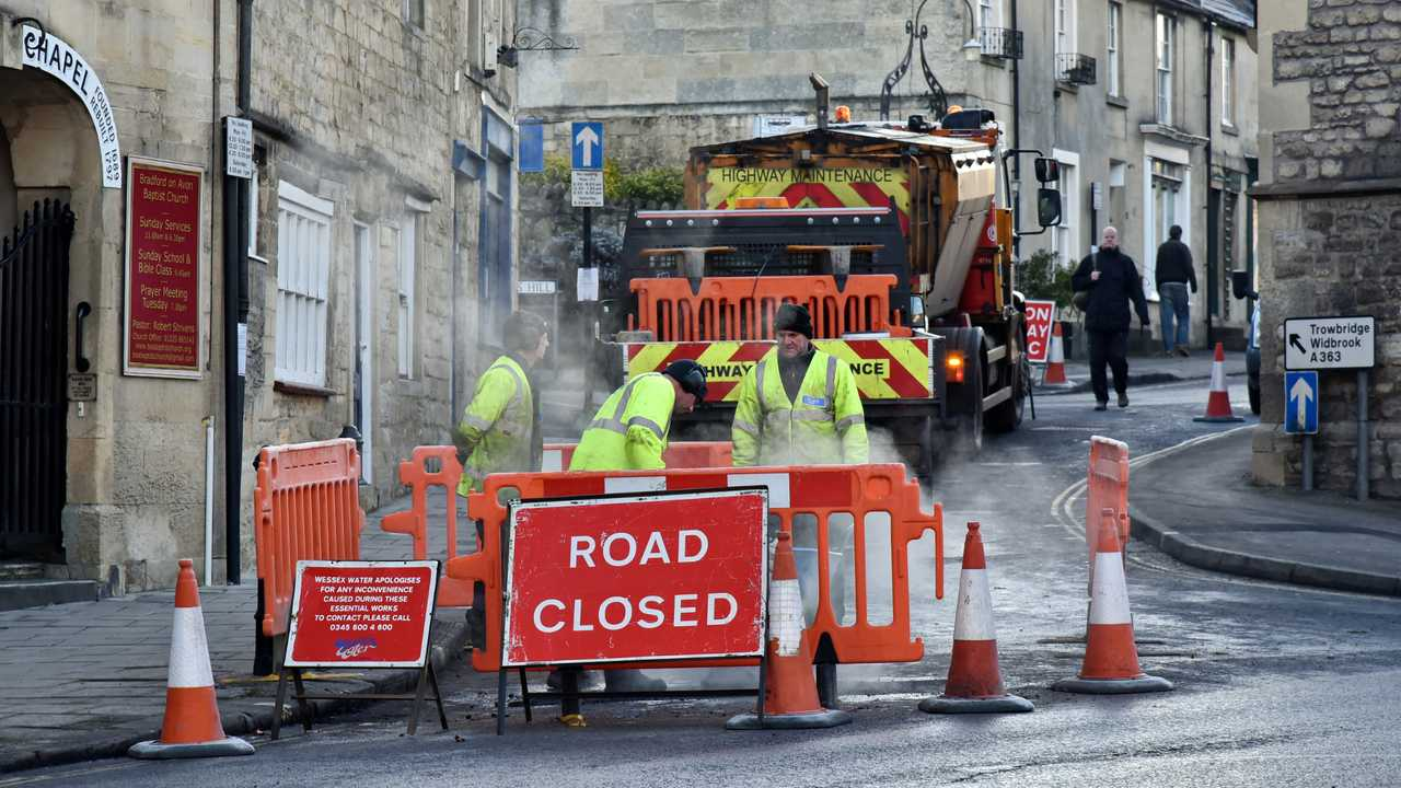 Road workers repairing road surface in Bradford on Avon UK town centre
