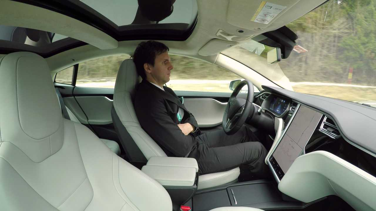 Man sitting in Tesla Model S with autonomous self driving autopilot engaged