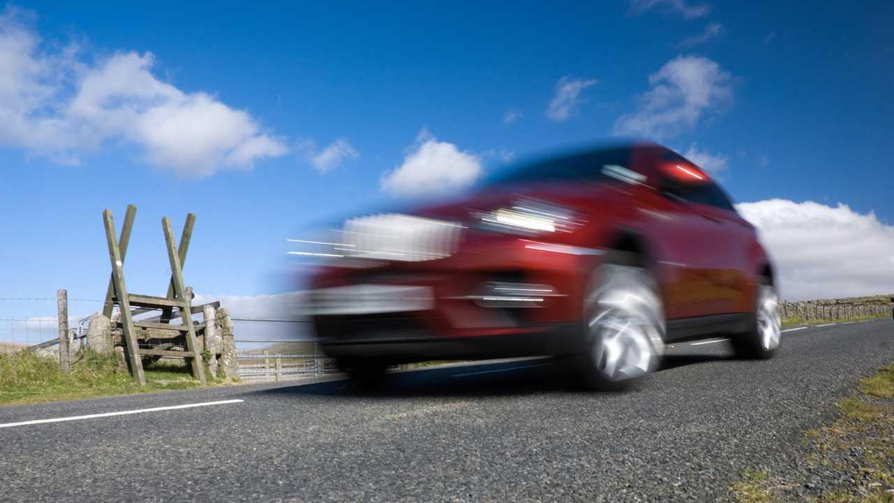Car speeding on empty mountain road in Dartmoor National Park Devon UK