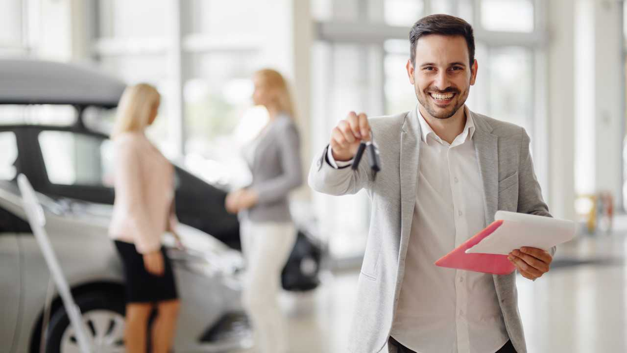 Salesperson handing over keys in dealership showroom