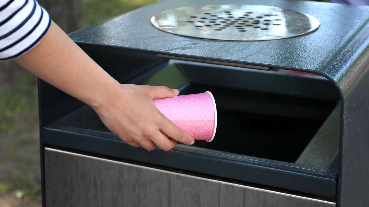 Woman throwing paper cup in litter bin outdoors