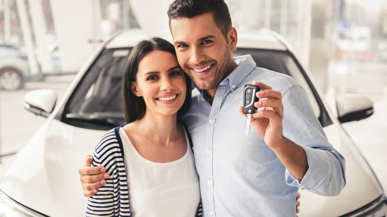 Young couple holding  key of their new car in dealership showroom