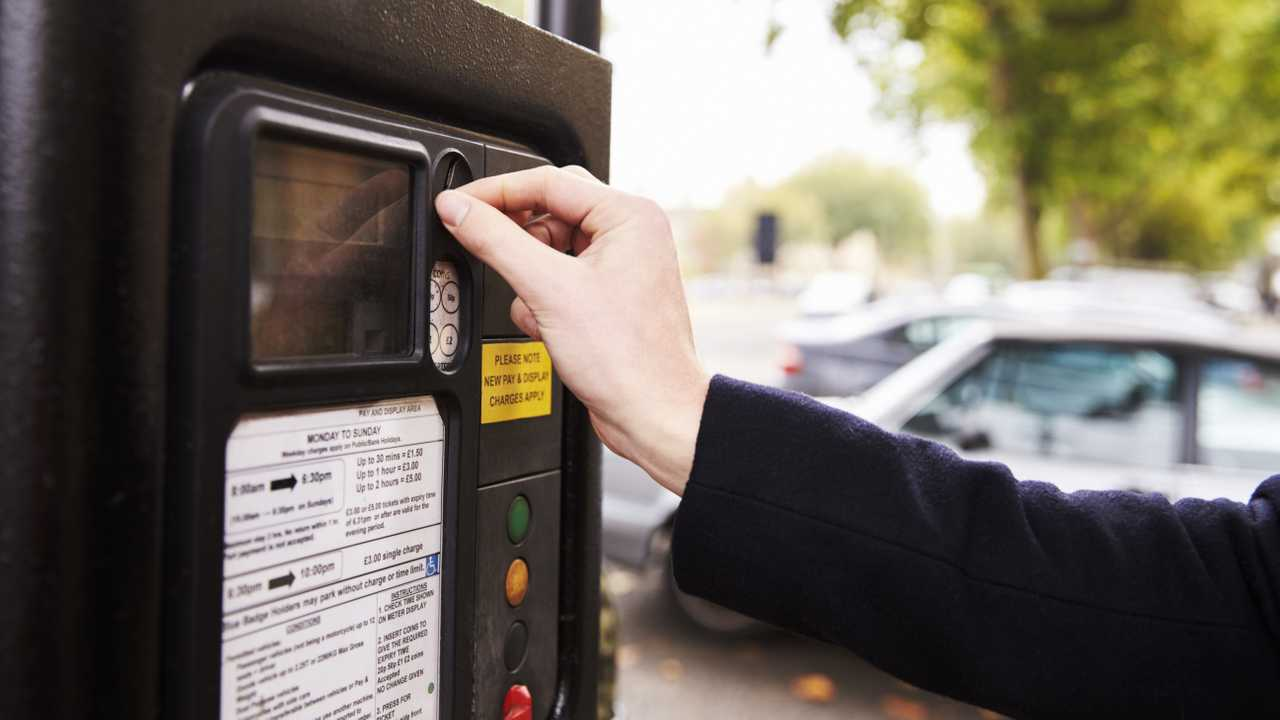 Man paying for parking on street using parking meter