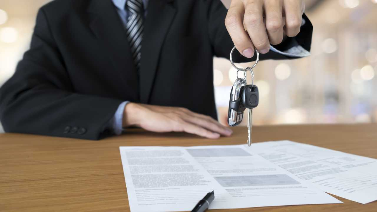 Car salesman handing keys over finance agreement documents