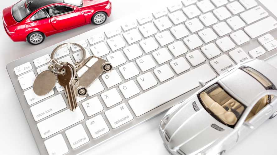 Car keys and toy cars on keyboard representing online car buying concept