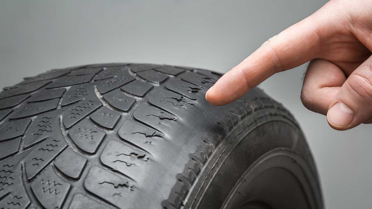 Man's finger pointing to damaged and worn tyre tread