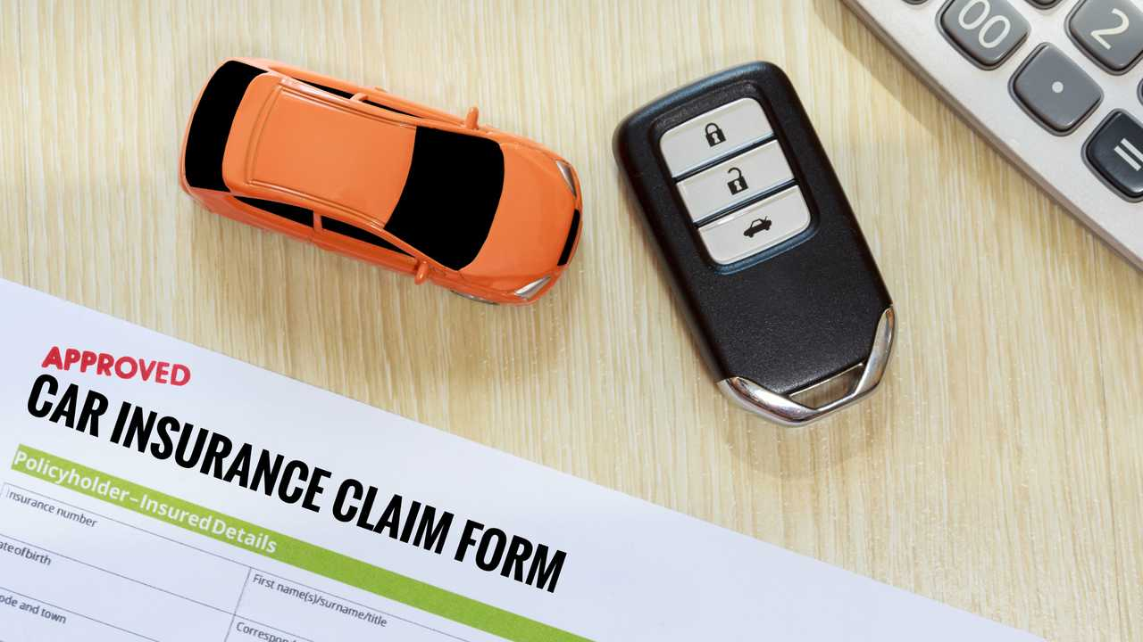 Top view of approved car insurance claim form with car key car toy and calculator