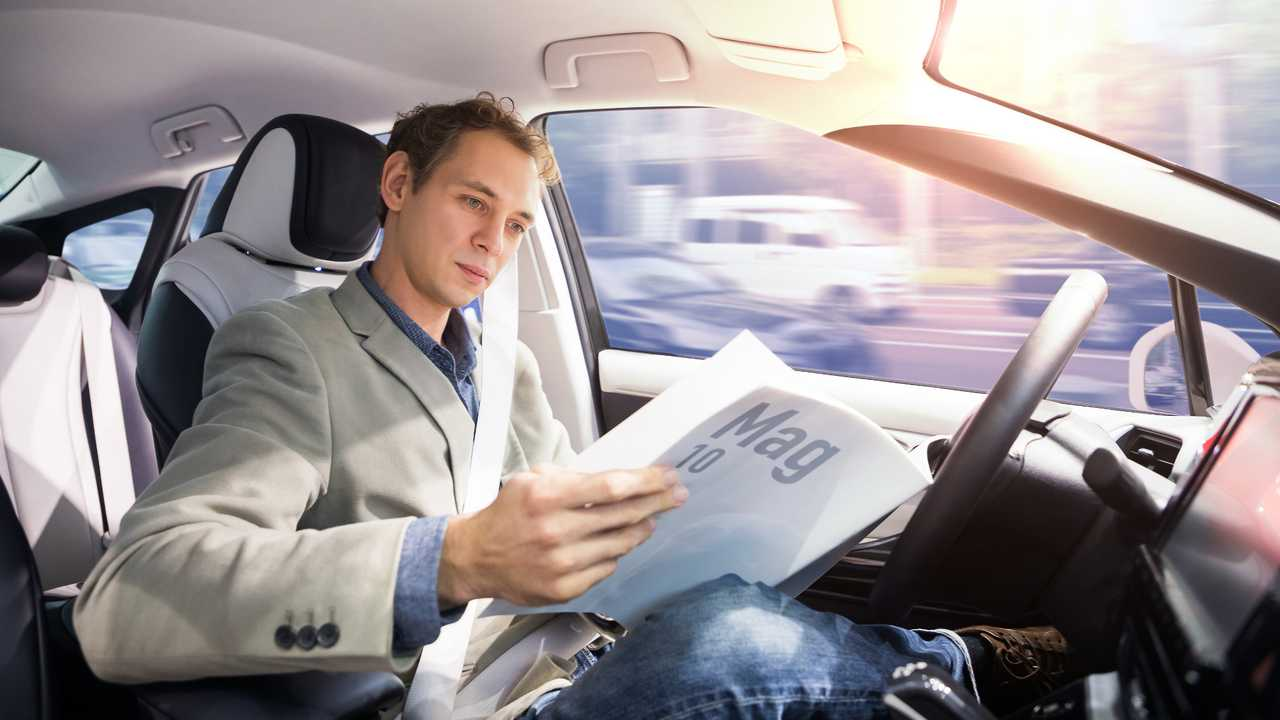 Man reading magazine in self driving autonomous car