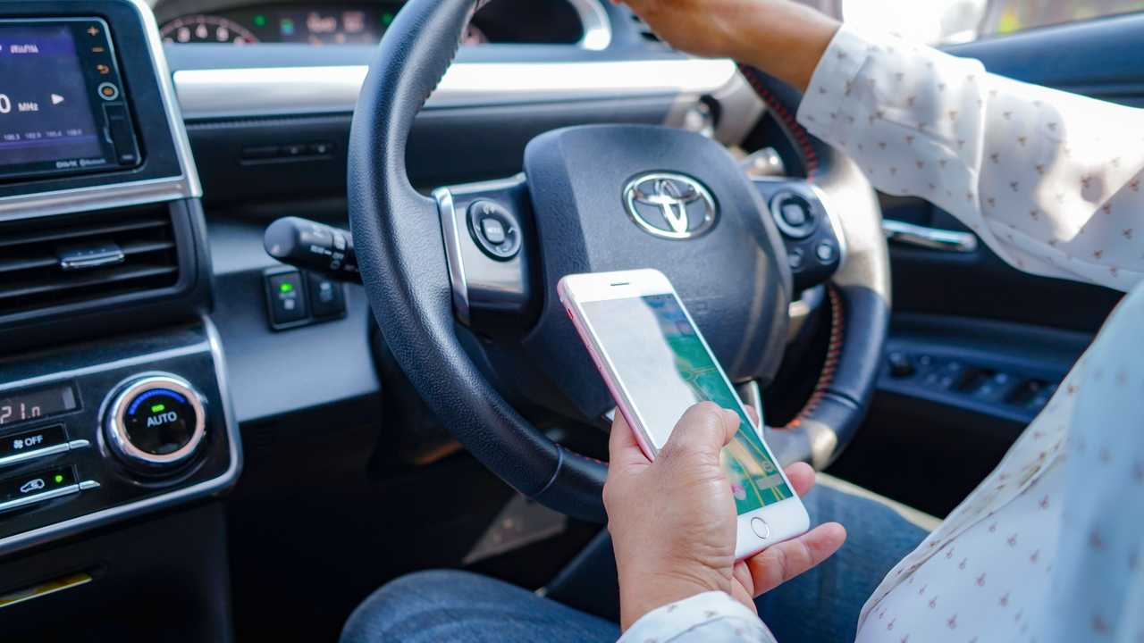 Man holding at smartphone while driving