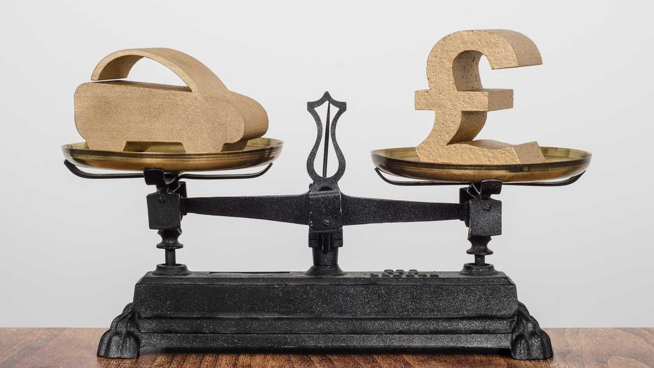 Car finance and pound symbols balance on scale