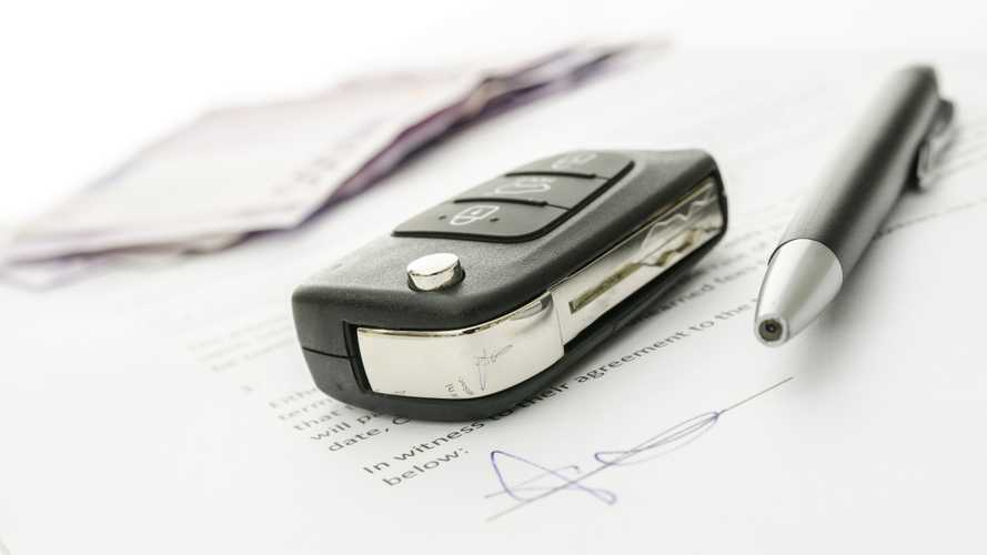 Car key and money on a signed contract of car sale