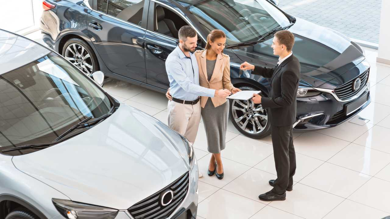 Car buyers signing contract for new car in auto showroom