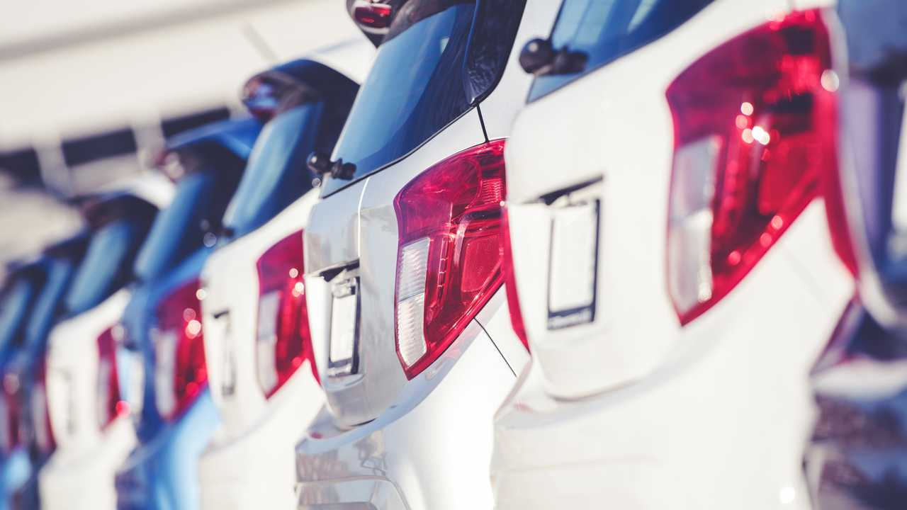 Row of new cars on dealership forecourt