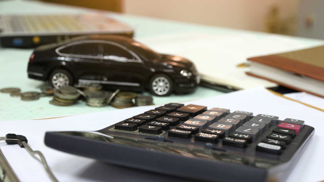 Finance and loan concept with car model calculator coins