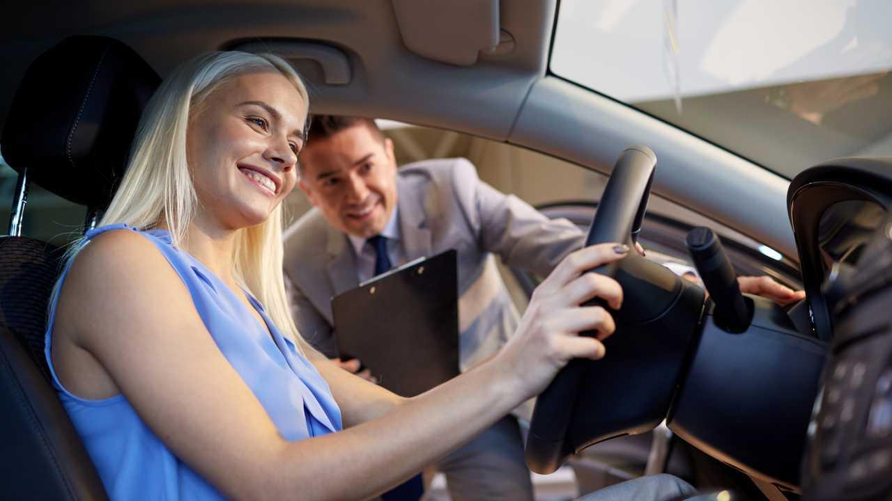 Car salesman showing woman car in dealership