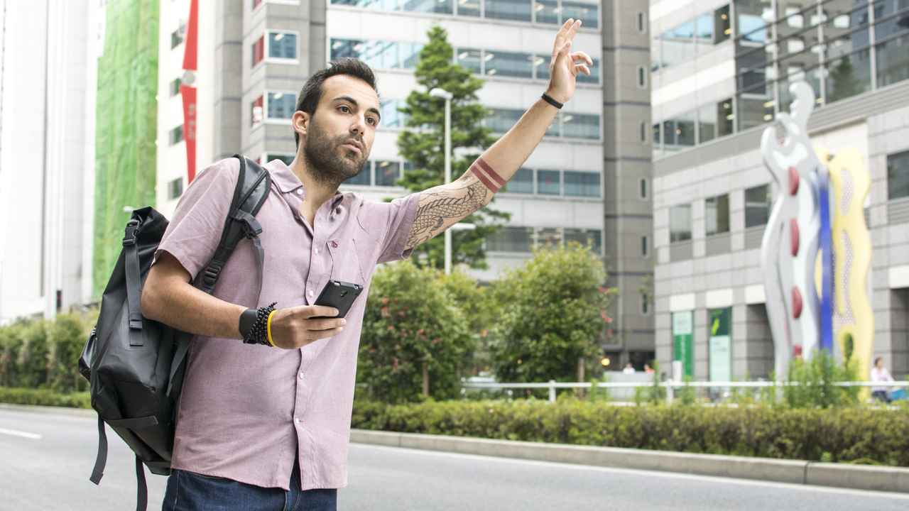 Young man hailing Uber taxi