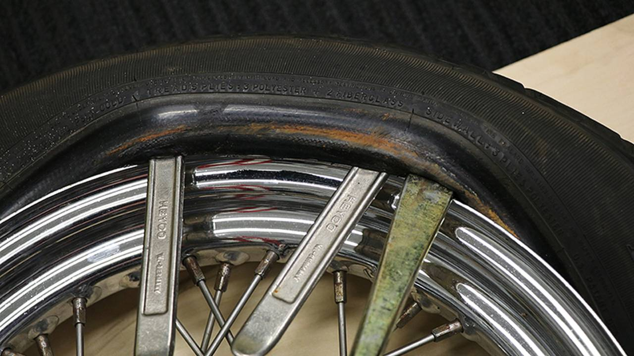 <em>The edge of tire will not just stay in place once it is levered up, so you'll need to use multiple spoons with some just holding the portion of the tire already levered past the rim as you work your way around the tire.</em>