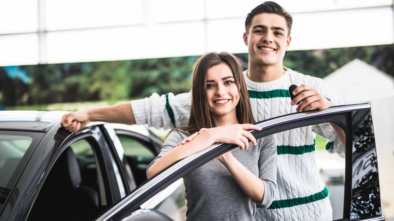 Smiling young couple buying a car at dealership