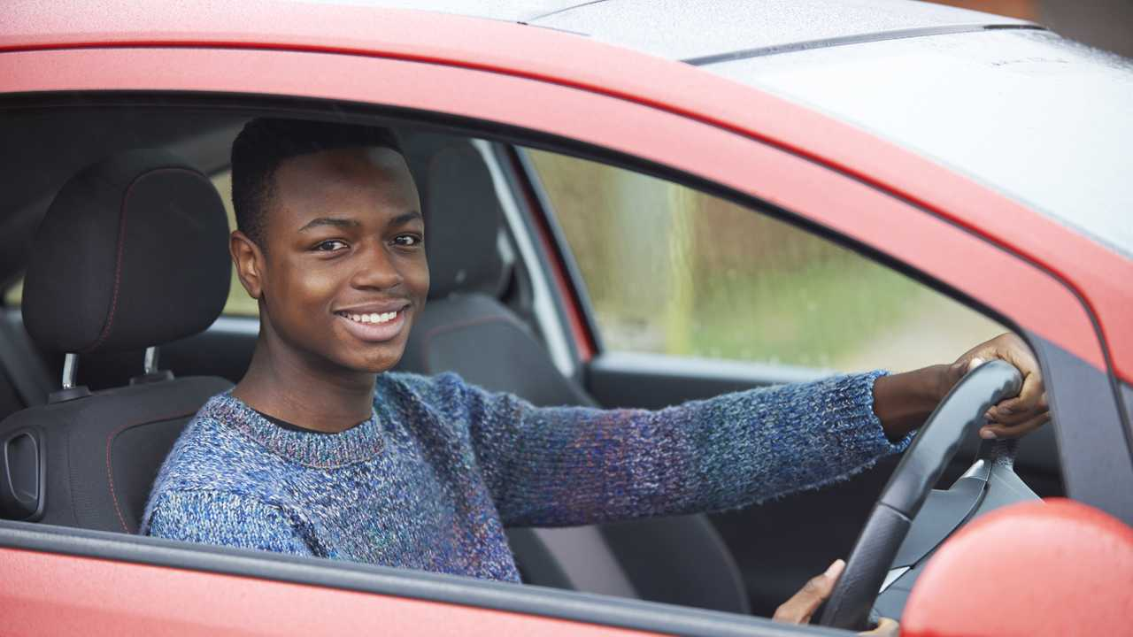 Newly qualified young man sitting in car