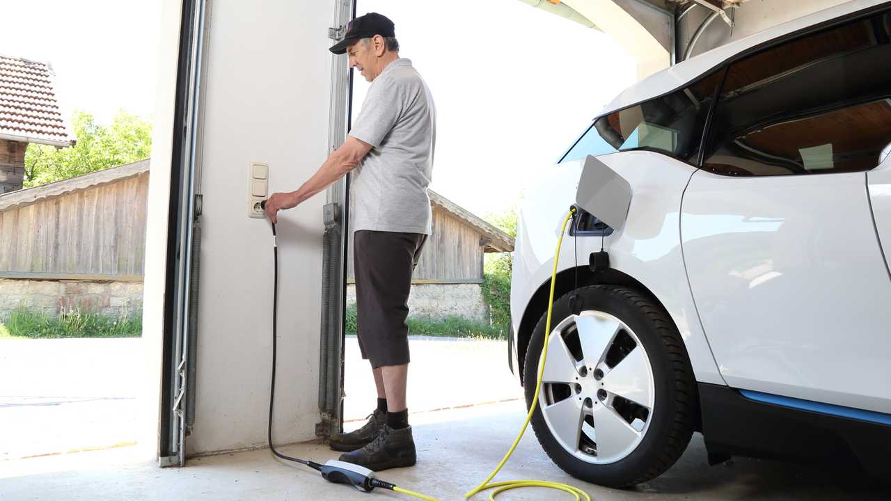 Man charging electric car at home