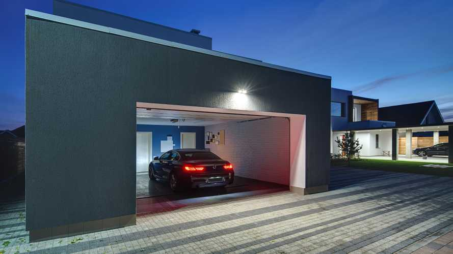 BMW 6 Series Gran Coupe sits in garage of modern country house with tiled driveway
