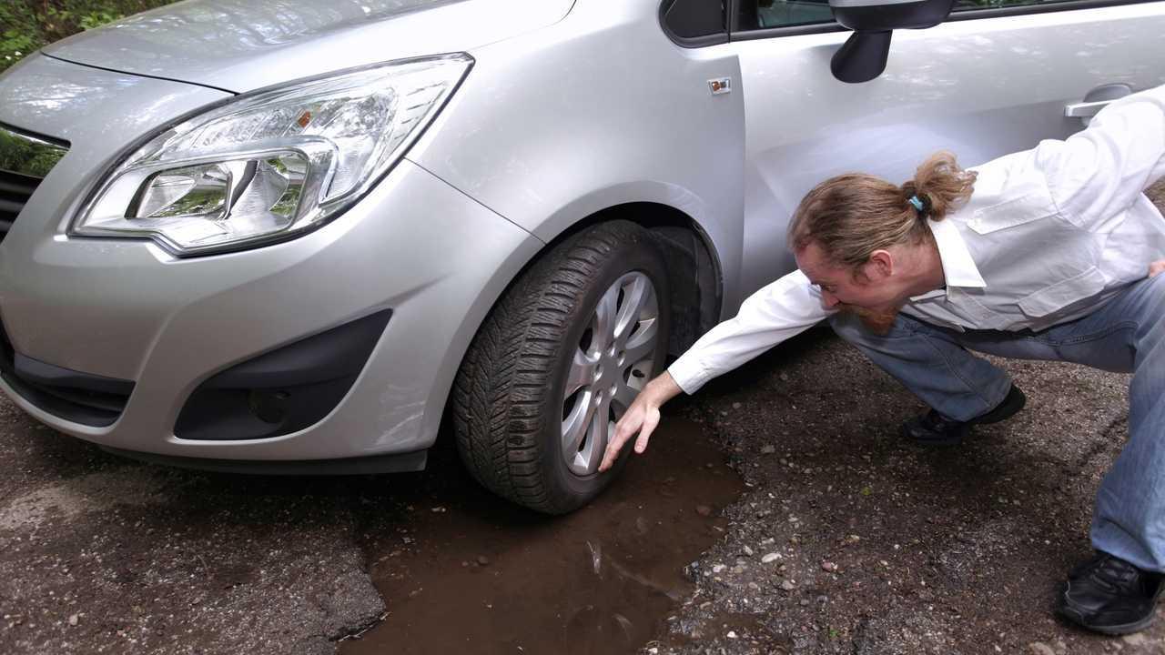 Upset driver inspecting wheel damaged  from potholes