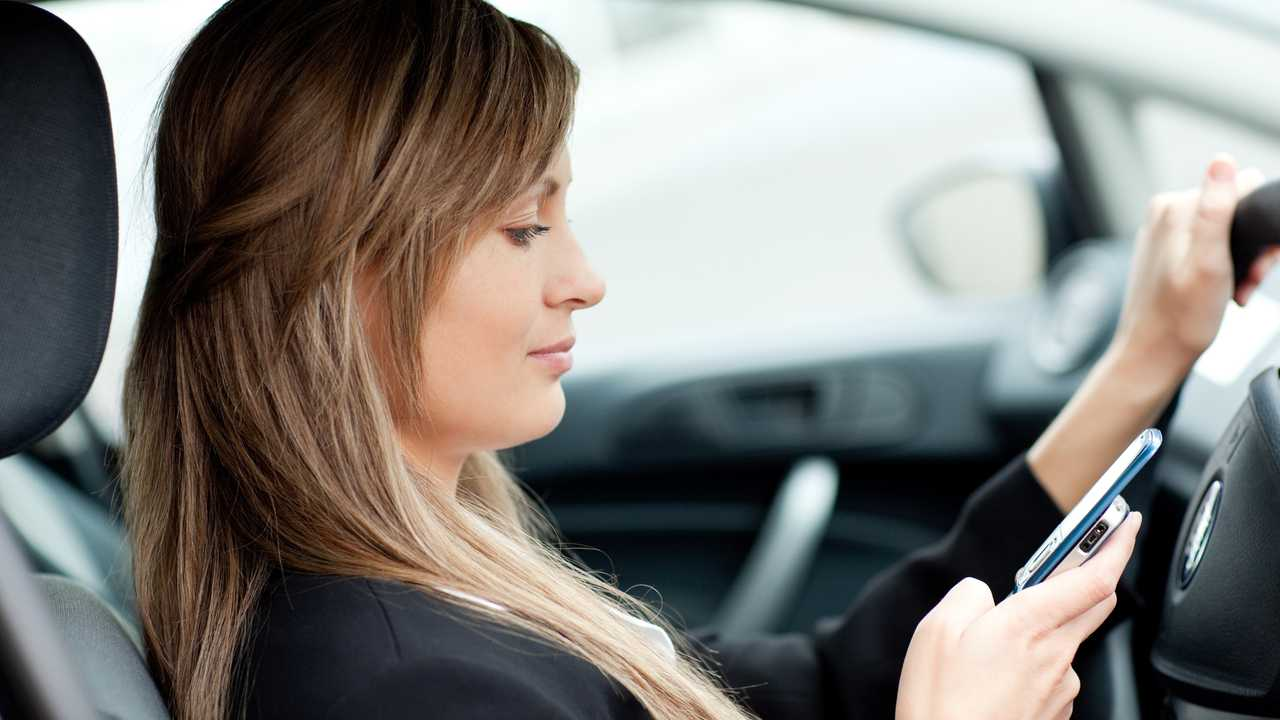Woman sending text while driving to work
