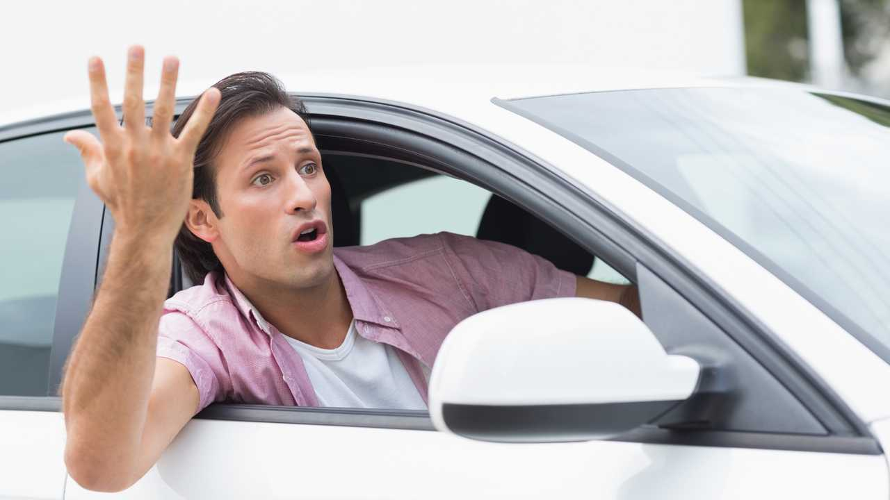 Young man experiencing road rage in his car