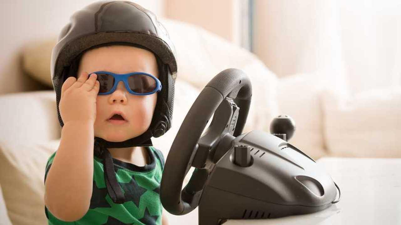 Toddler wearing helmet playing with video game steering wheel