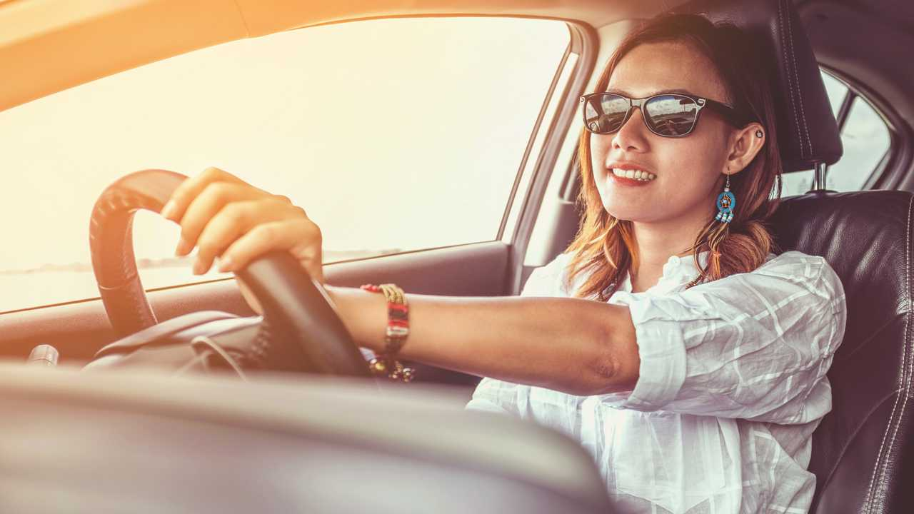 Woman in a happy mood driving a car