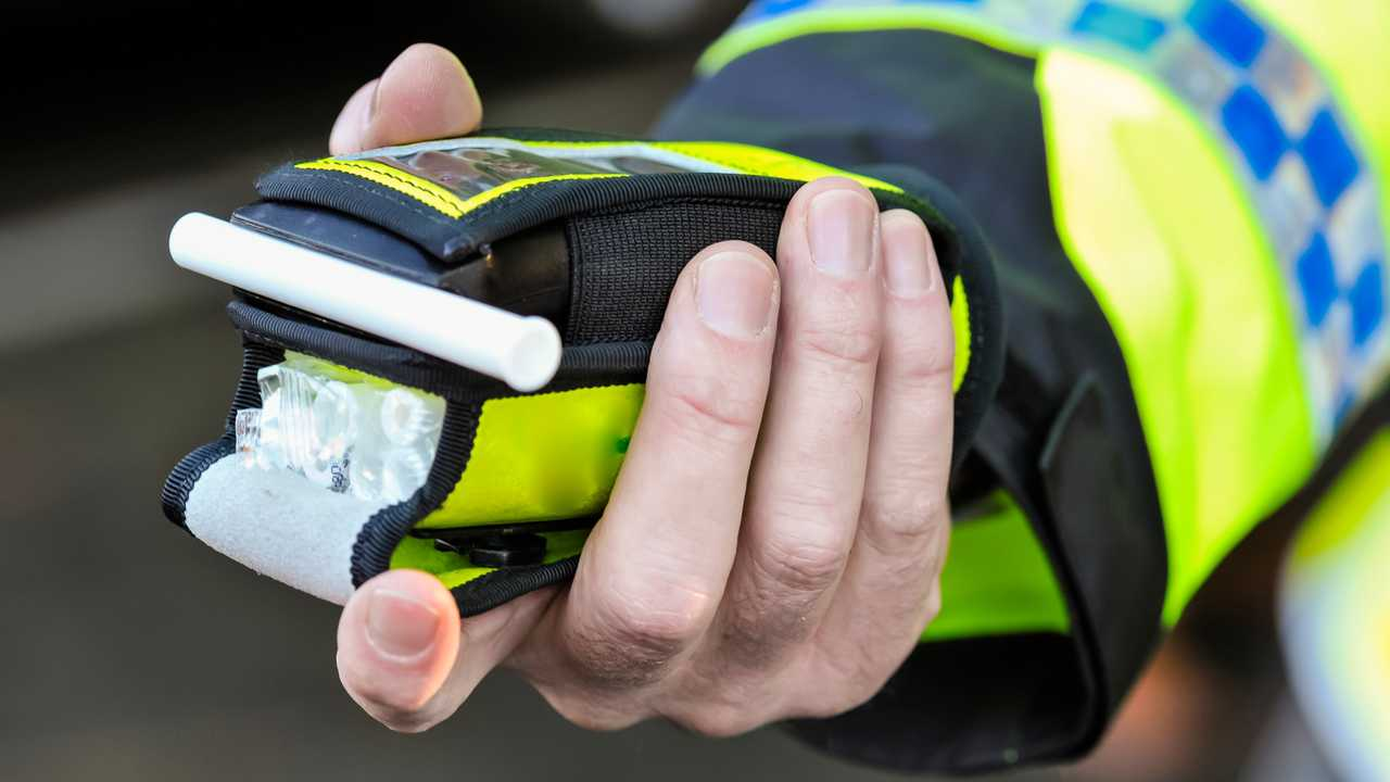 Belfast police officer holds breathalyser alcohol breath test device
