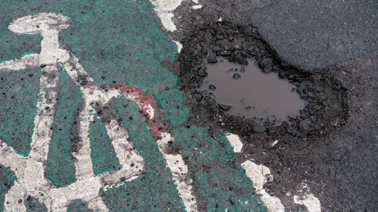 Large deep pothole in road surface adjacent to cycle path