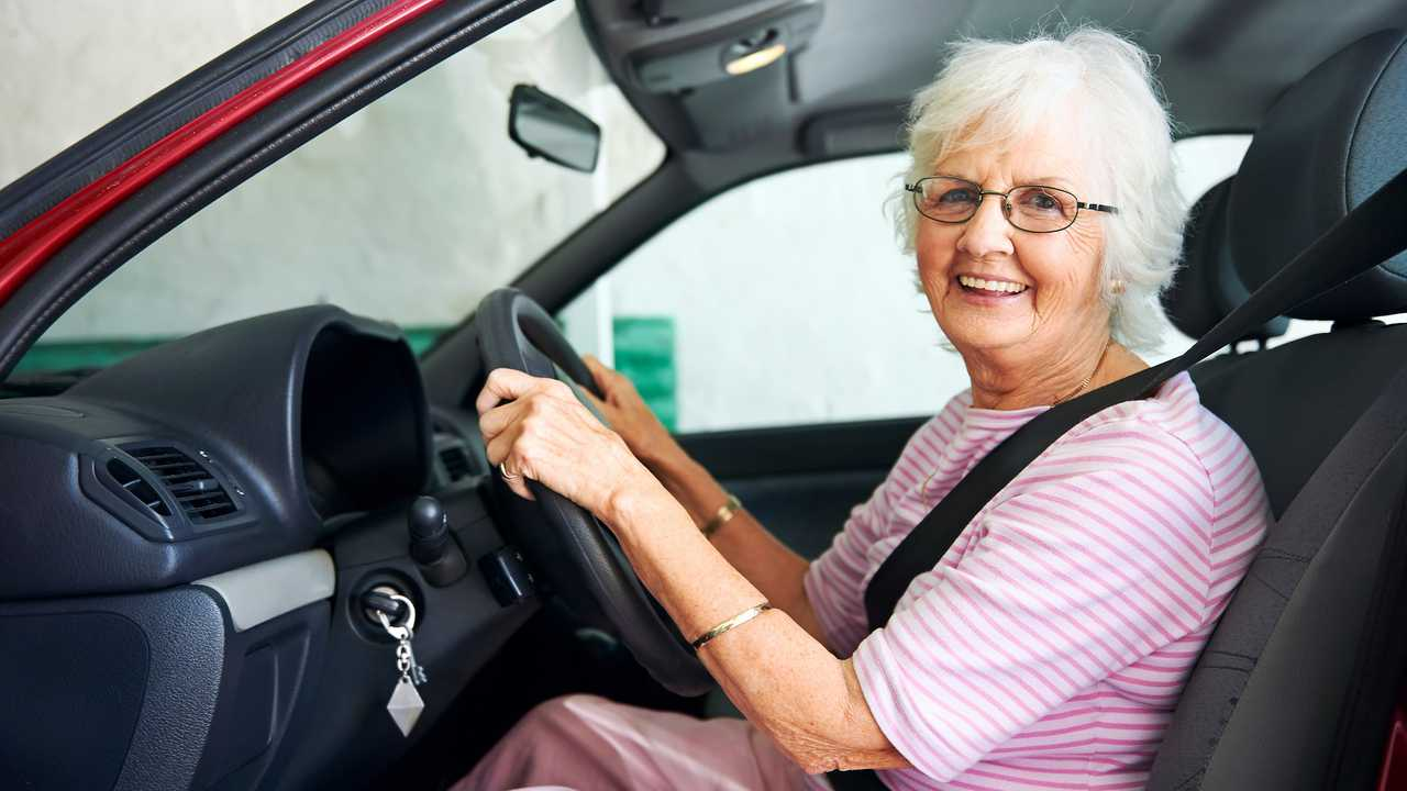 Smiling senior woman sitting in a vehicle