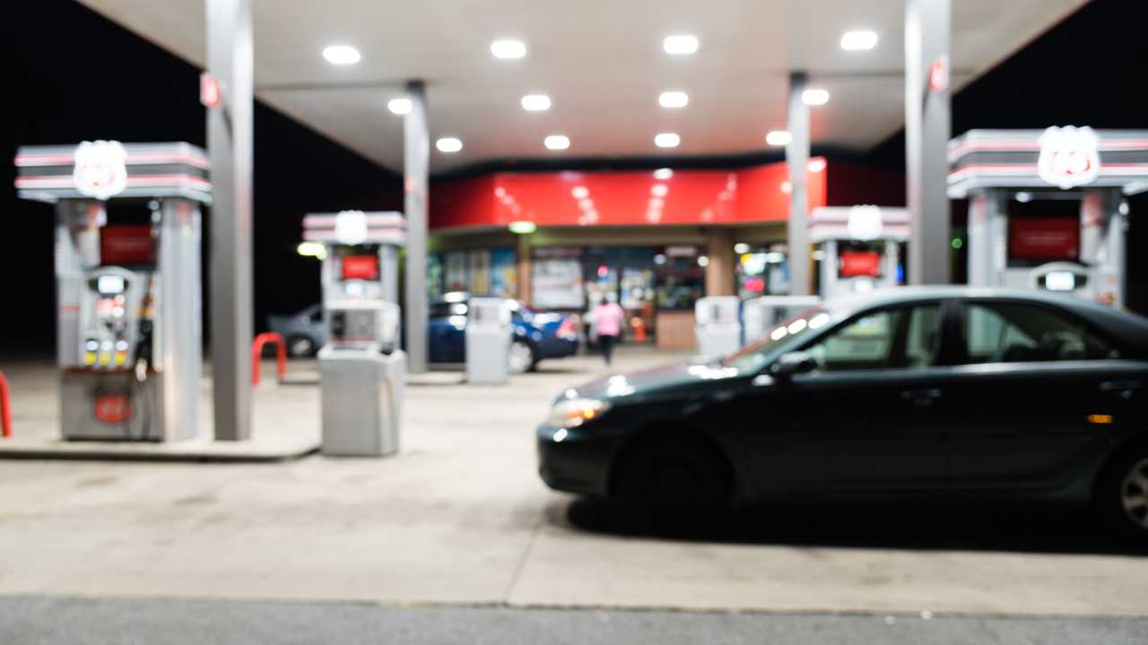 Petrol station with car refuelling at night