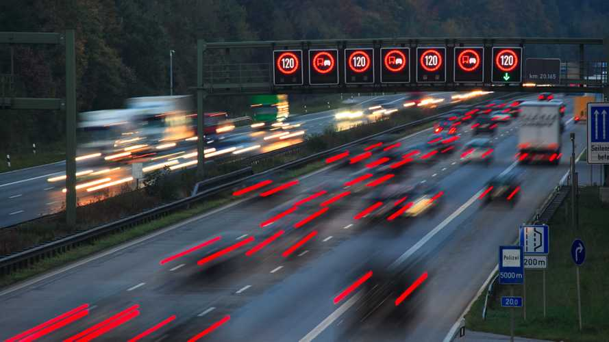 Night traffic on autobahn with speed limit signs