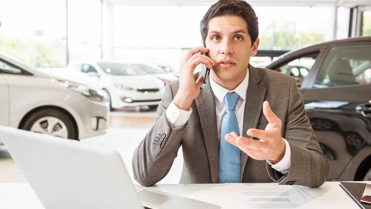 Salesman having phone call in new car showroom