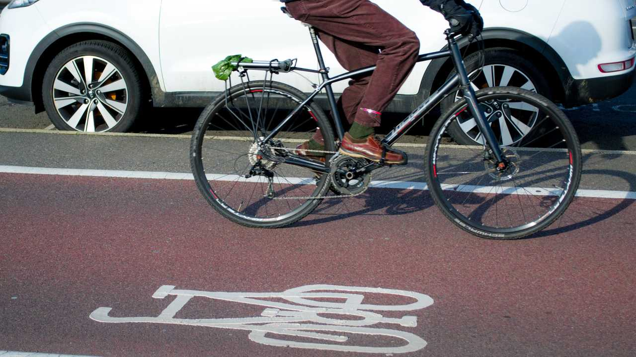 Man riding bicycle on cycle path next to cars