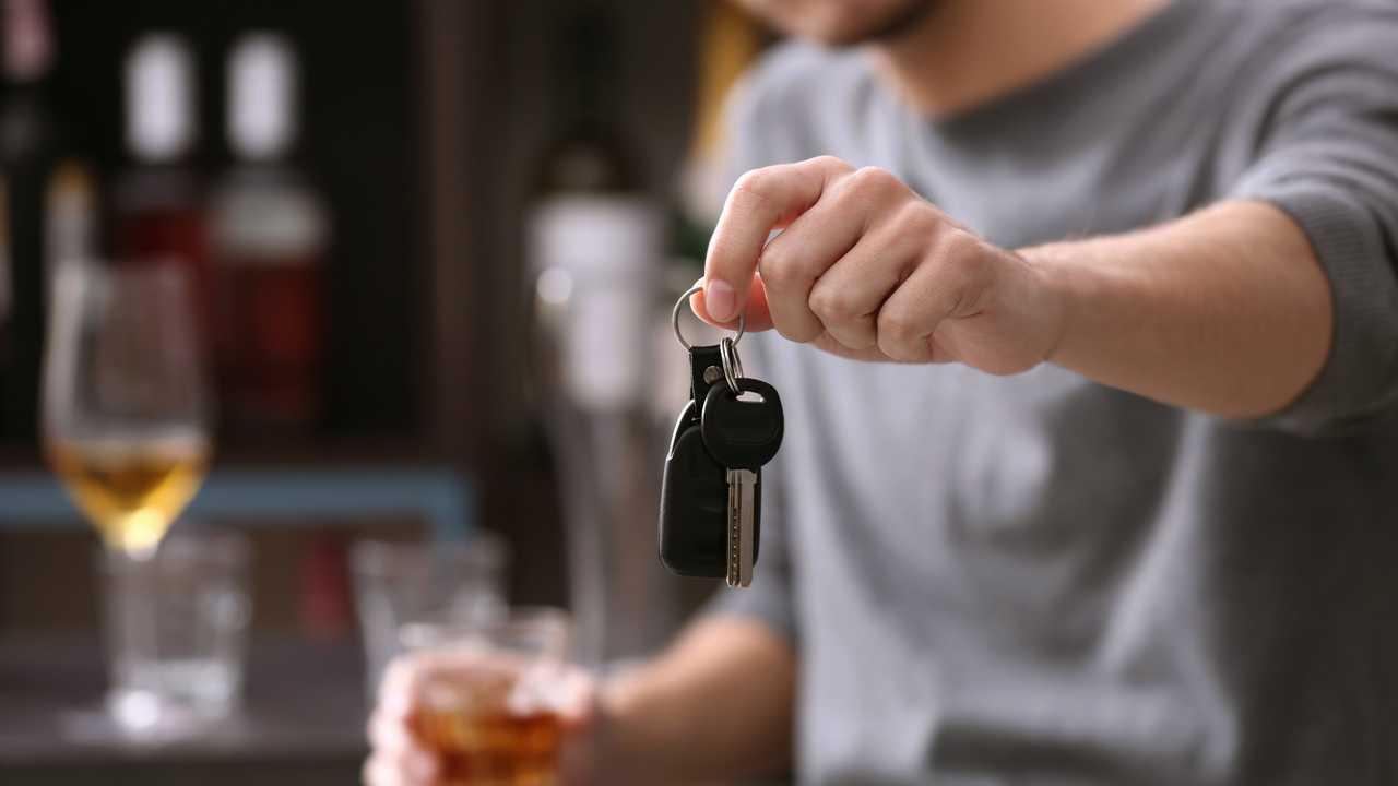 Man holding car key and alcoholic beverage