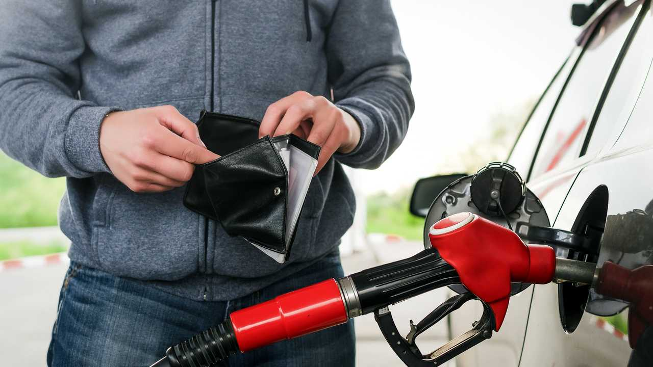 Man checks empty wallet for money at petrol station pump