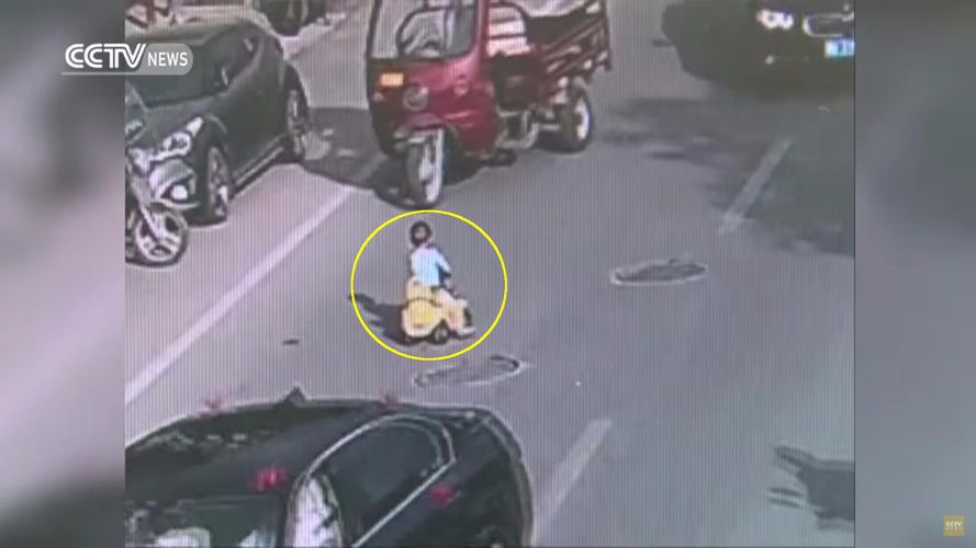 Toddler rides toy car down busy Chinese highway