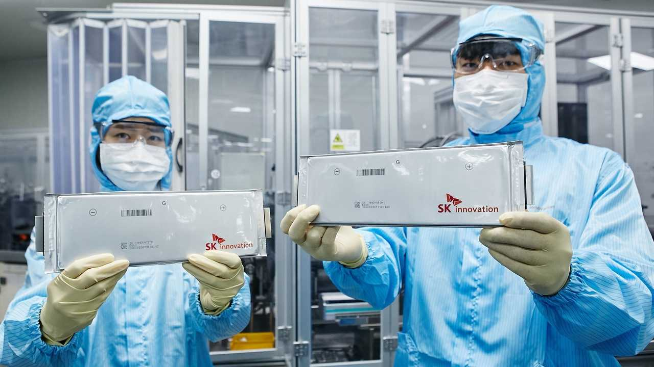 SK innovation researchers hold up EV battery cells