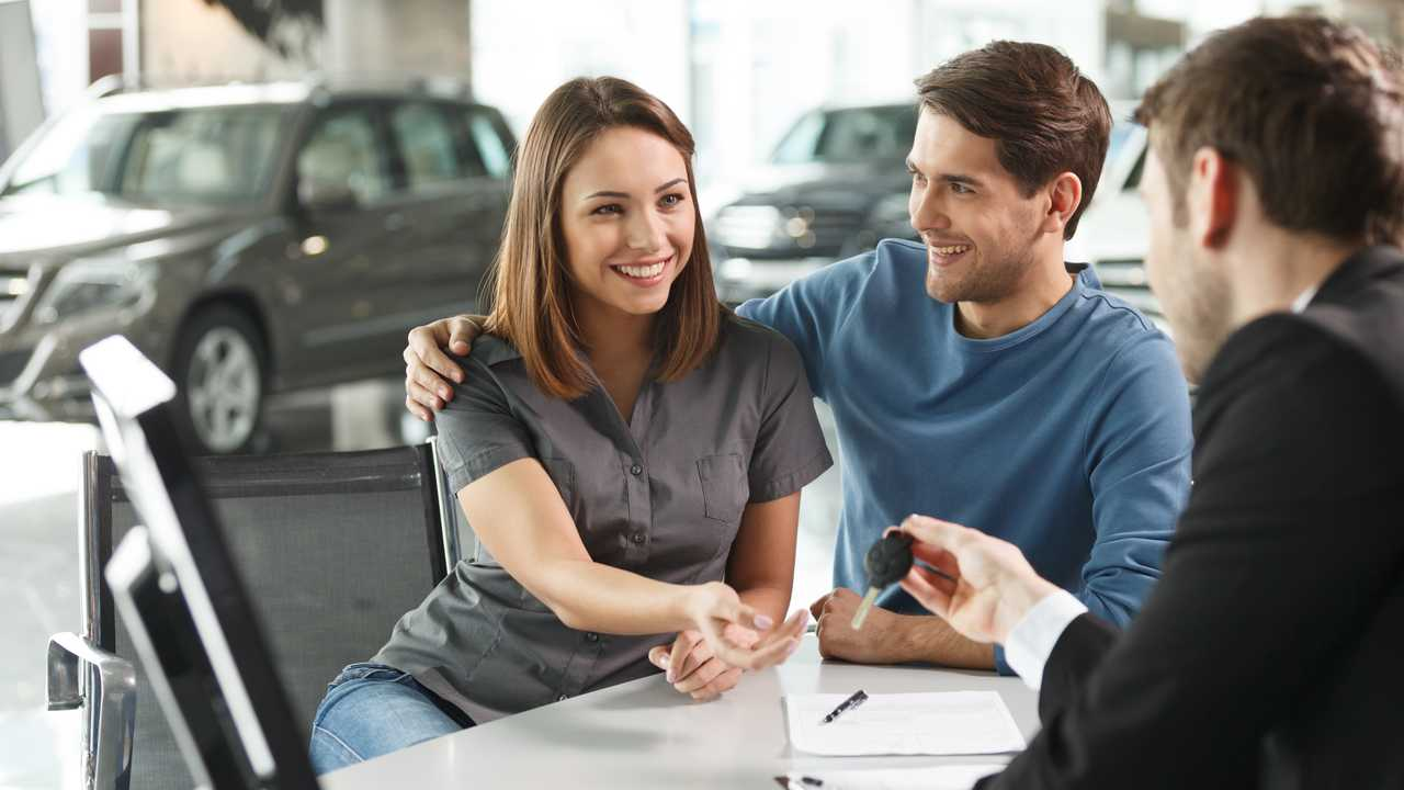 Car salesman giving keys of new car to young couple