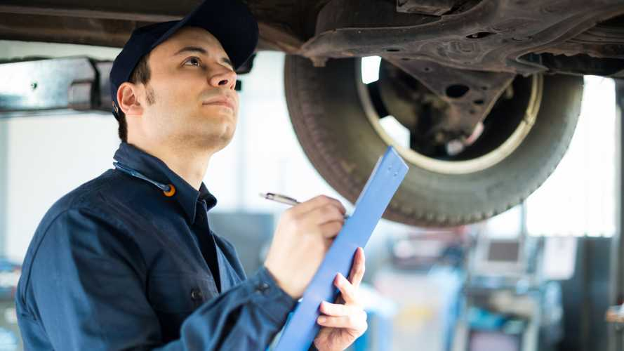 Mechanic taking notes while inspecting a car