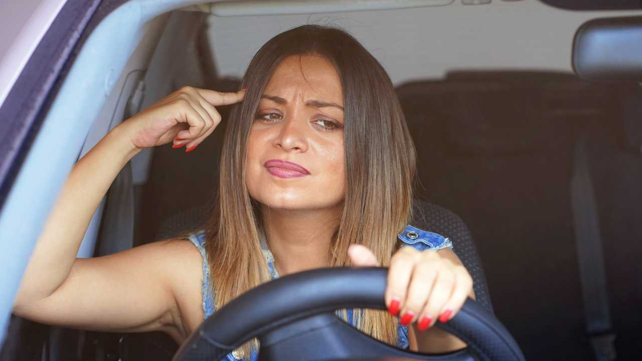 Angry woman using hand gesture driving car