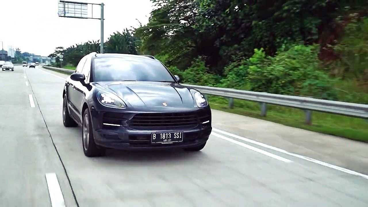 Porsche Macan melintas cepat di jalan tol.