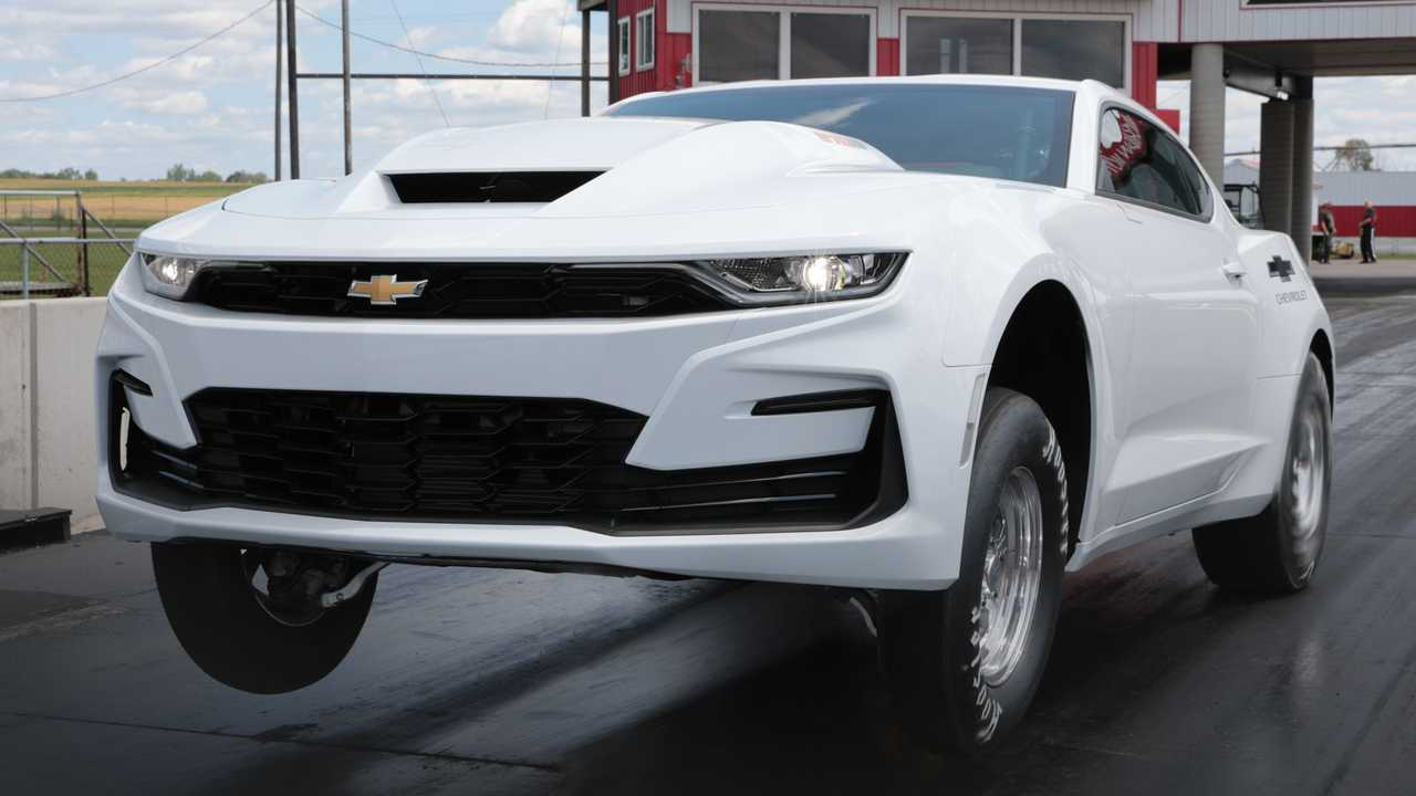 A 2022 Chevrolet COPO Camaro launches from the starting line at a drag strip.