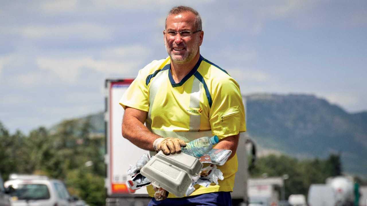 Agent d'autoroute ramassant des déchets