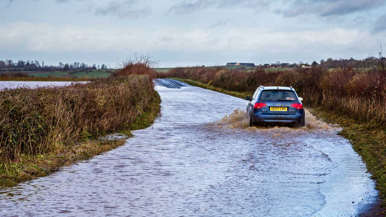 Car driving through flooded road near Nunney in Somerset UK