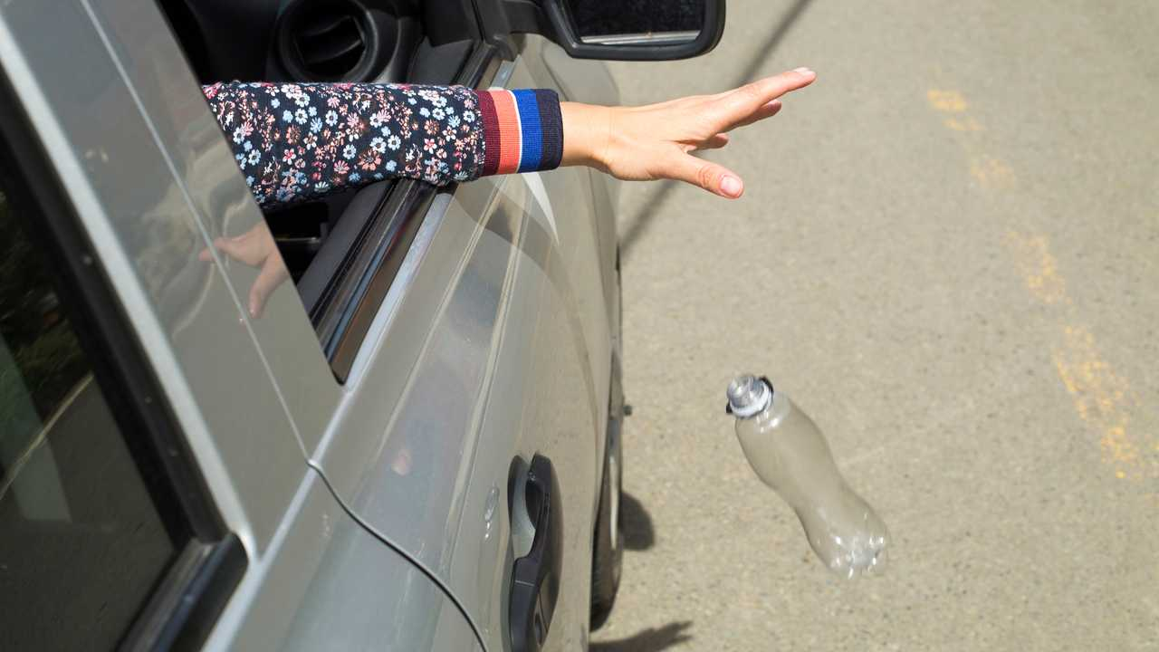 Driver throws plastic bottle from the car